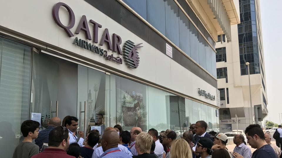 People gather outside a branch of Qatar Airways in the United Arab Emirate of Abu Dhabi on June 6, 2017. A ban on Qatari flights imposed by Saudi Arabia and its allies took effect as first efforts were made to resolve the biggest feud to hit the Arab world in years.