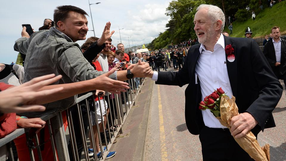 Britain's main opposition Labour Party leader Jeremy Corbyn greets supporters as he leaves after attending a campaign visit in Colwyn Bay, north Wales, on June 7, 2017, on the eve of the general election. Britain on Wednesday headed into the final day of campaigning for a general election darkened and dominated by jihadi attacks in two cities, leaving forecasters struggling to predict an outcome on polling day.