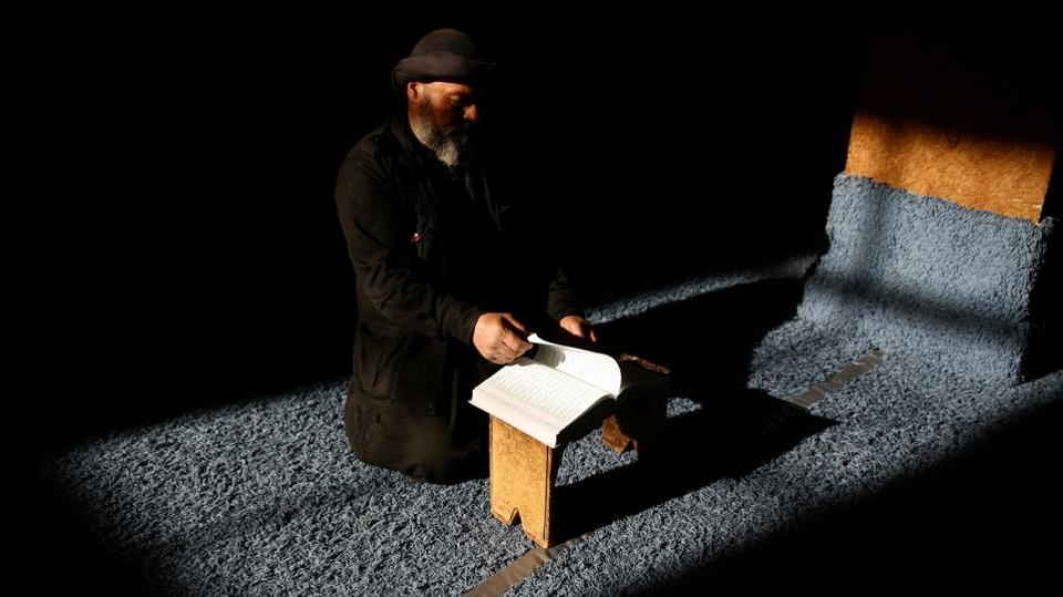 A man reads the Quran during Ramadan in the rebel held Damascus suburb of Ghouta. (REUTERS)