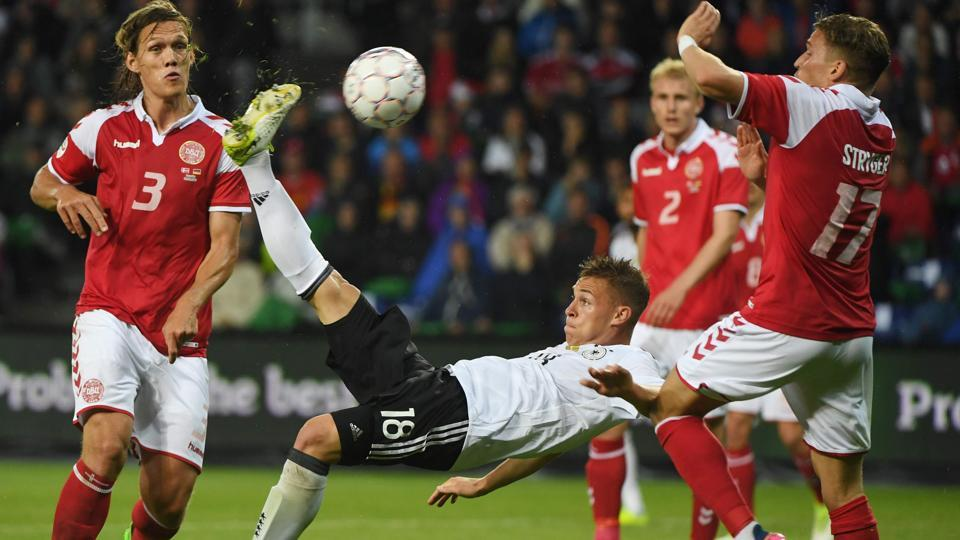 Germany national football team defender Joshua Kimmich scores past Denmark football team´s Jannik Vestergaard (L) and Jens Stryger Larsen (R) during the friendly football match in Brondby, Denmark, on Tuesday.