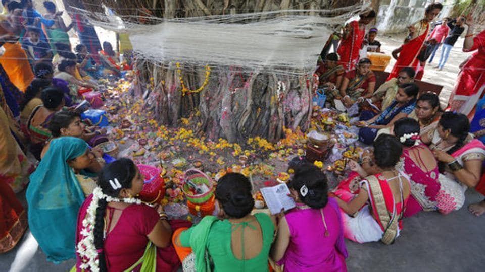 Women perform rituals around a Banyan tree on the first day of the festival. These rituals are an inspiration from a legendary story of a woman called Savitri, who wins her husband back to life from the god of death `Yama,' by her sheer determination and devotion. (Ajit Solanki / AP)