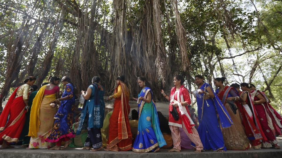 Women in groups move together to offer prayers to the banyan tree. Ganga water is poured and threads of red or yellow colour are tied around the tree chanting prayers. (Ajit Solanki / AP)