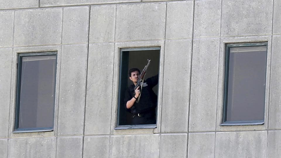 An armed man stands at a window of the parliament building in Tehran on June 7, 2017. Several attackers stormed Iran's parliament and a suicide bomber targeted the shrine of Ayatollah Ruhollah Khomeini killing a security guard and wounding several others. The Islamic State so far has claimed responsibility for attack at Iranian parliament.   (AP)