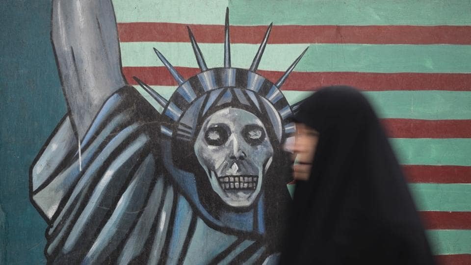 An Iranian woman walks past an anti-US mural painted on the wall of the former US Embassy, Tehran.