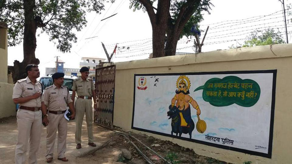 Superintendent of Police -Kathik S (extreme right) before a wall painting displaying safety message  in Lohardaga