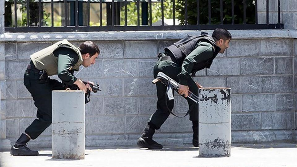 Members of Iranian forces take cover during an attack at the Iranian parliament building. (REUTERS)
