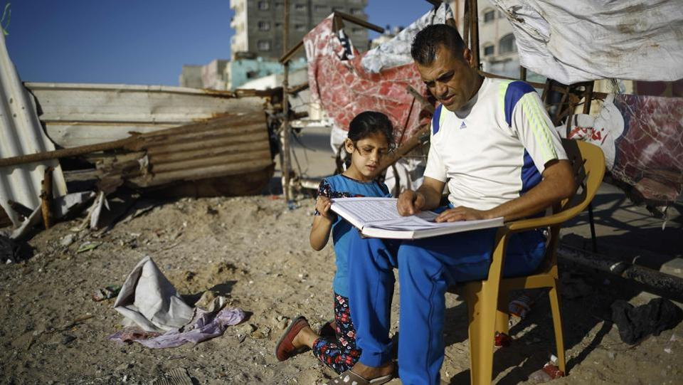 A Palestinian man reads a copy of the Quran, to a young girl at Al-Shatee refugee camp in Gaza City. (AFP)