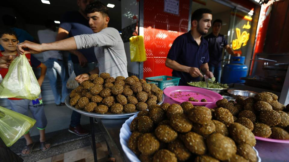 A Palestinian street vendor sells falafel at his stall during Ramadan in Gaza City. Savoury snacks are popular choices for breaking the fast at sunset throughout the Middle-East. (AFP)