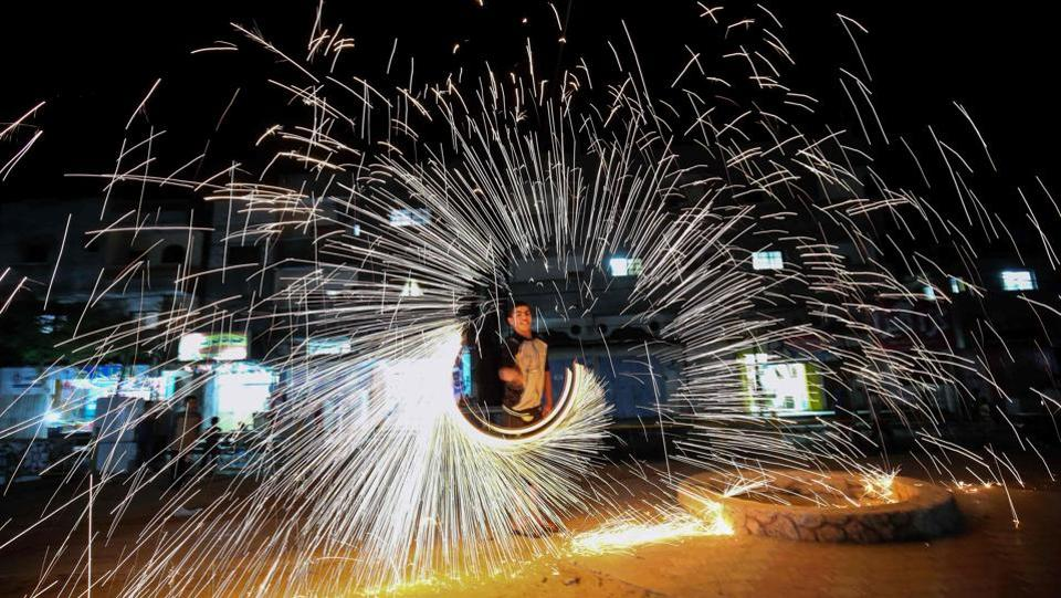 A Palestinian man plays with fire crackers celebrating Ramadan at the town of Rafah in the southern Gaza Strip. (AFP)