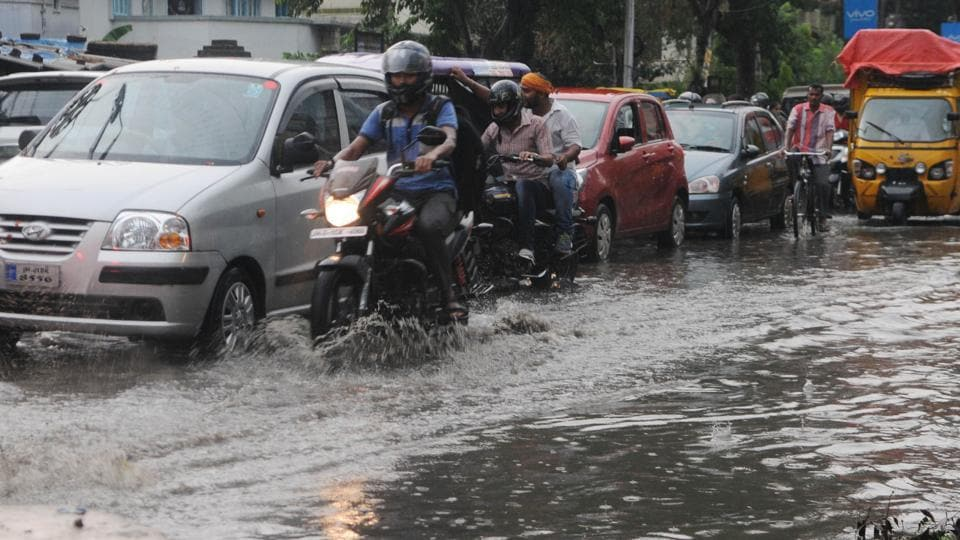 Commuters passing through a waterlogged area after pre-monsoon rain in Ranchi,