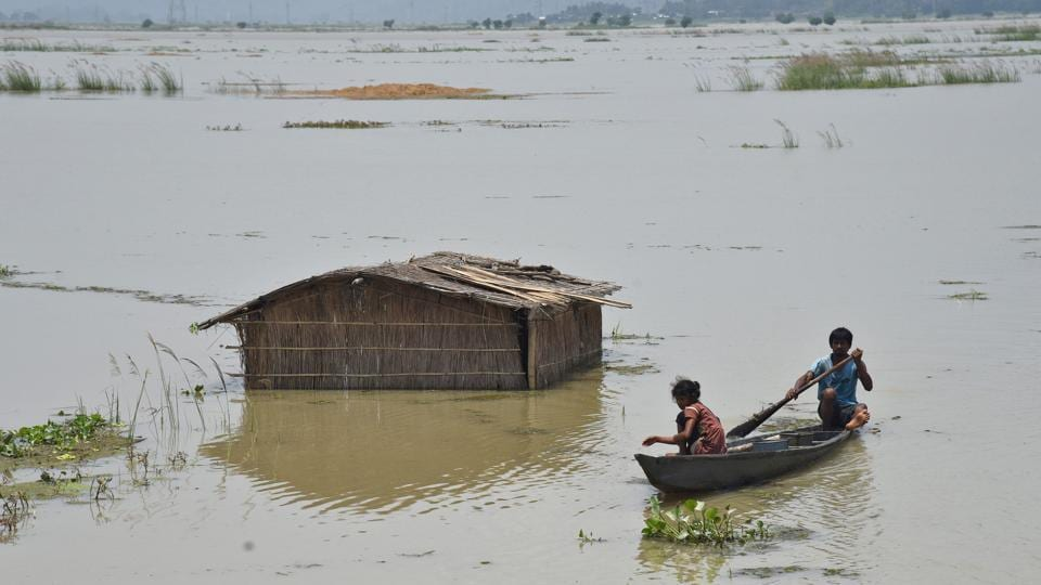 A boy rows a boat past a submerged hut in a flooded field at Mayong village.  (Anuwar Hazarika / REUTERS)