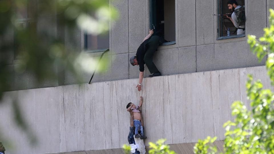 Iranian policemen evacuate a child from the parliament building in Tehran on June 7, 2017 during an attack on the complex.