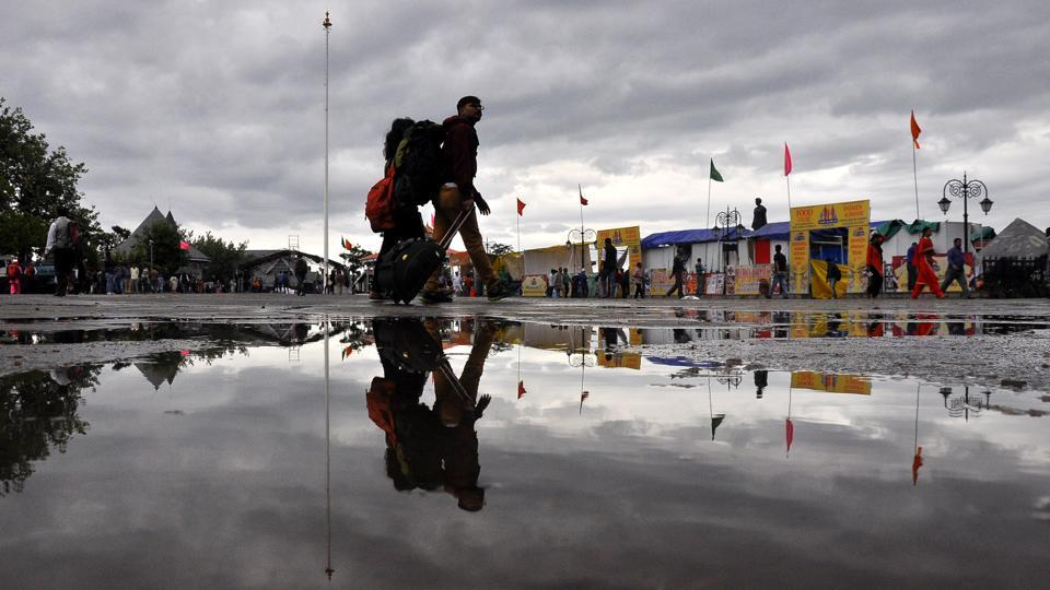 Tourists take a stroll in the cloudy weather after heavy rain  at Ridge, Shimla.  (Deepak Sansta / HT Photo)