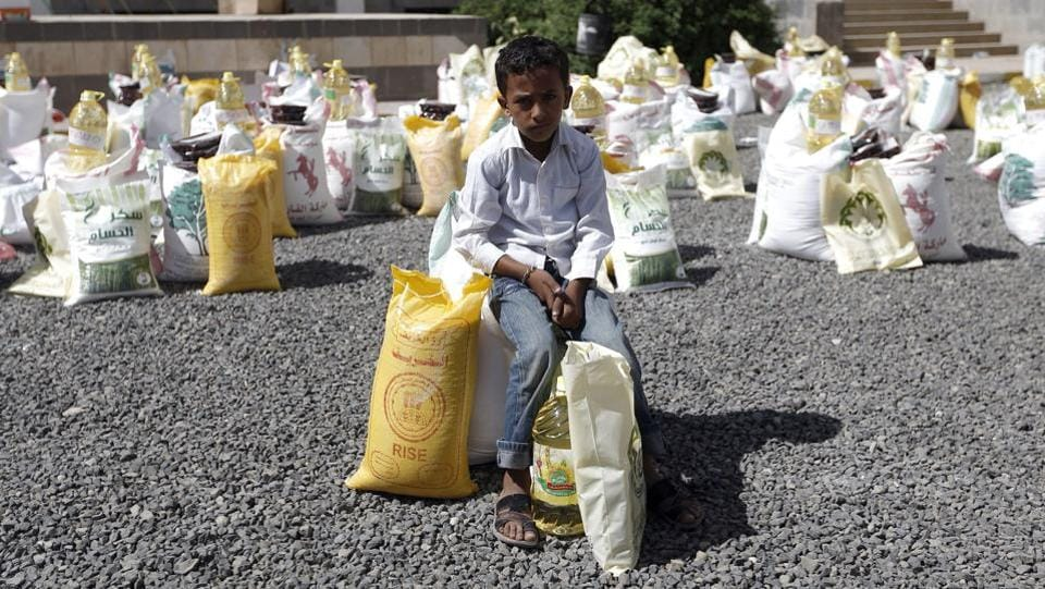 A Yemeni boy sits next to food aid distributed by a local charity during the Muslim holy fasting month of Ramadan, in the capital Sanaa. (AFP)