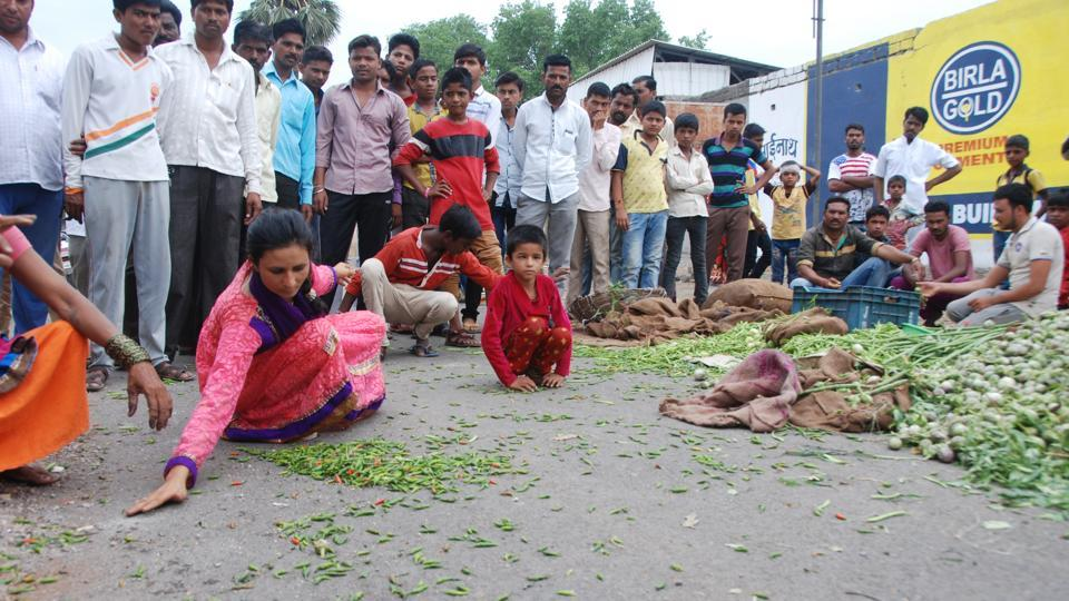 Villagers gather vegetables dumped on the road by farmers during a protest in Aurangabad, Maharashtra in June. Farmers in the state have so far rejected Chief Minister Devendra Fadnavis's offer for a waiver by October and rejected the plan for making sales below the support price illegal, demanding expedited resolution.  (ht photos)