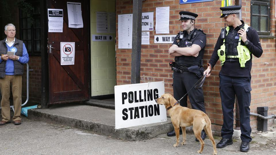 Police officers stand outside a polling station in Maidenhead, England before Britain's Prime Minister Theresa May arrived to vote in the general election. (Alastair Grant / AP)