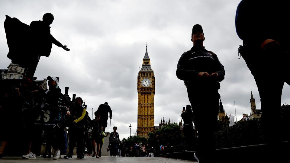 People walk around Parliament Square on election day in Westminster, London, on June 8, 2017. Polling stations opened across Britain on Thursday amid heightened security worries following a series of terror attacks in what one senior police official described as