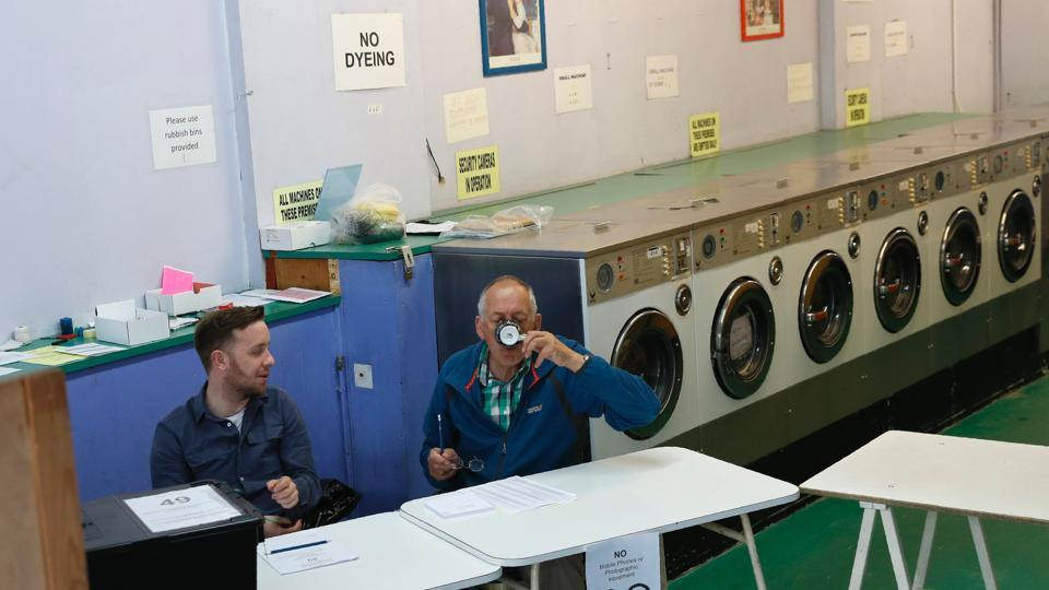 A presiding officer (R) and poll clerk wait for early morning voters at a Polling Station set up in a launderette and nail bar in Headington outside Oxford, west of London. (Adrian Dennis / AFP)