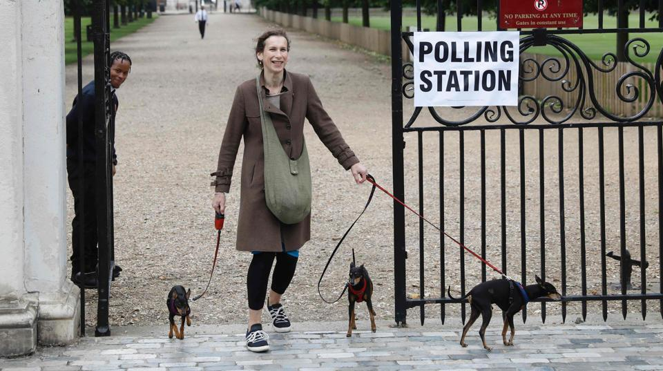 A woman with three dogs leaves the polling station at Burton Court pavilion in southwest London  (Odd ANDERSEN / REUTERS)