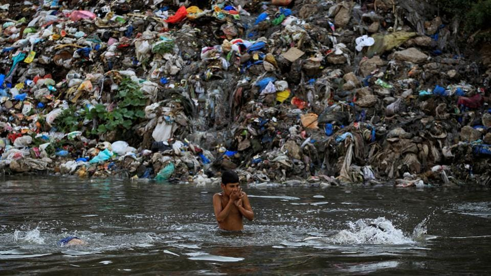 A child swims in a polluted river with a mound of trash in the background in Rawalpindi, Pakistan. (Caren Firouz/REUTERS)