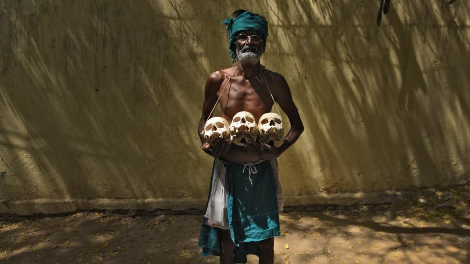 Palanichamy, a farmer from Tamil Nadu holds the skulls of those who allegedly committed suicide back home during the protest demanding aid from government in New Delhi, in May. The farmers' novel means of protest garnered widespread attention in the media. (Ravi Choudhary/HT PHOTO)