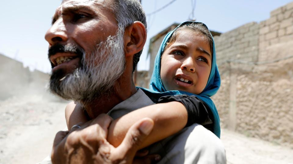 A man carries his daughter on his back after fleeing their home due to fighting between the Iraqi forces and Islamic State militants in Mosul's al-Zanjili's district in Iraq. Mosul Iraq Federal Police forces evacuated many Iraqi families from a western Mosul district where battles approach the birthplace of the Islamic State's proclaimed 'caliphate'. (Erik De Castro / Reuters)