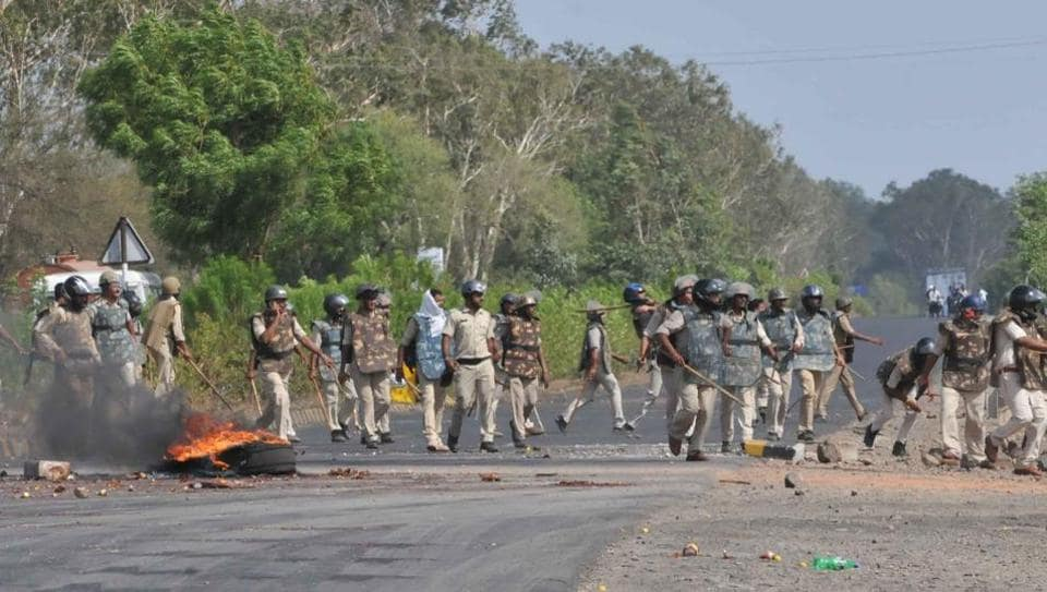 Police try to clear the Mhow-Neemuch highway in Mandsaur in Madhya Pradesh where protesters burnt tyres and pelted stones at officials.