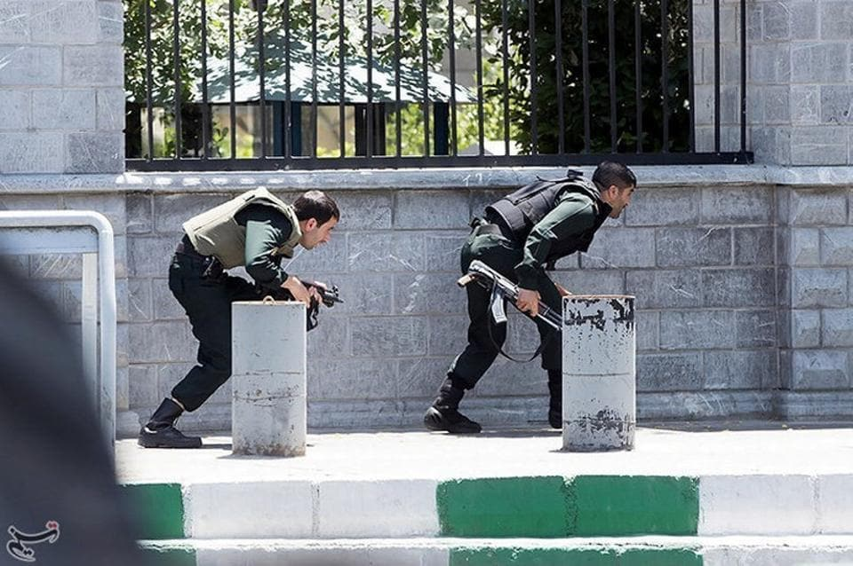 Iranian forces take cover during an attack on the Parliament on Wednesday