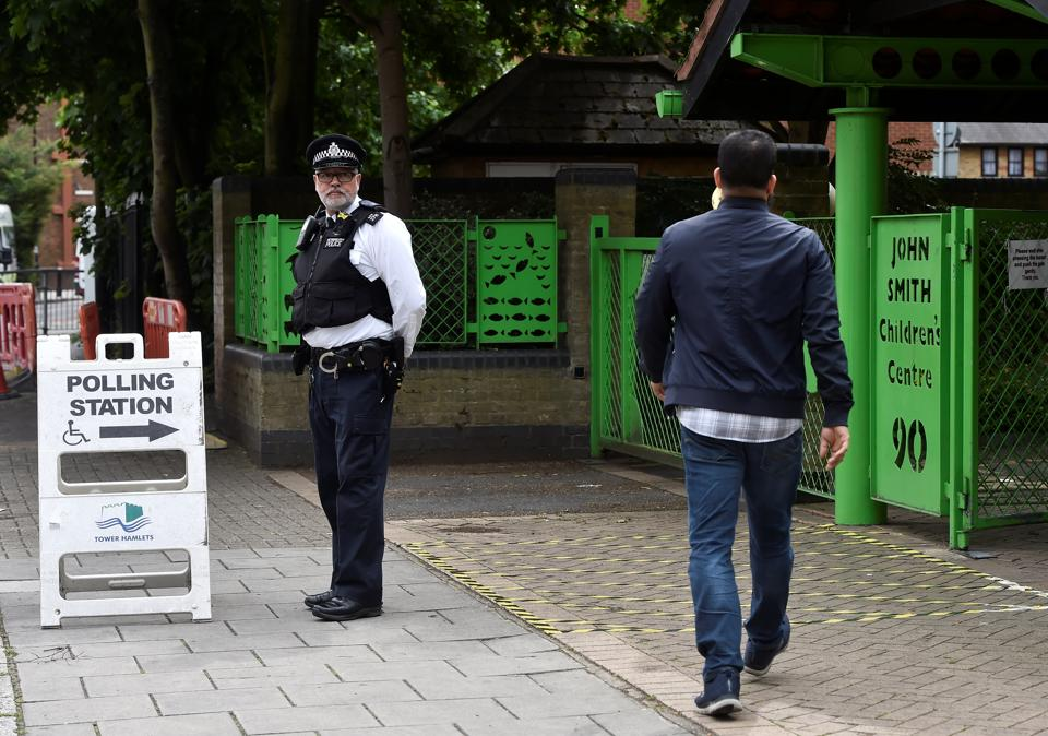 A police officer stands on duty outside a polling station in London on Thursday.