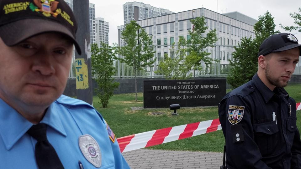 A guard (L) and a police officer are seen in front of the U.S. embassy in Kiev, Ukraine, June 8, 2017.