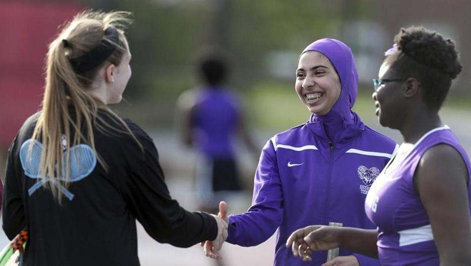 In this May 24, 2017 photo Tabarek Kadhim, center, congratulates an opponent after a tennis match in Windham, Maine. Deering High School is providing sport hijabs with the goal of making Muslim girls comfortable and boosting their participation in sports.