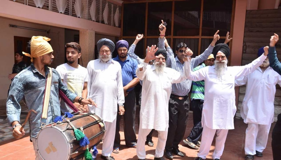 Villagers and relatives of Tanmanjeet Singh Dhesi, the first turbaned Sikh MP in Britain's House of Commons, celebrating his victory as by distributing sweets and dancing to the beat of the dhol at his native Raipur village in Jalandhar district on Friday.