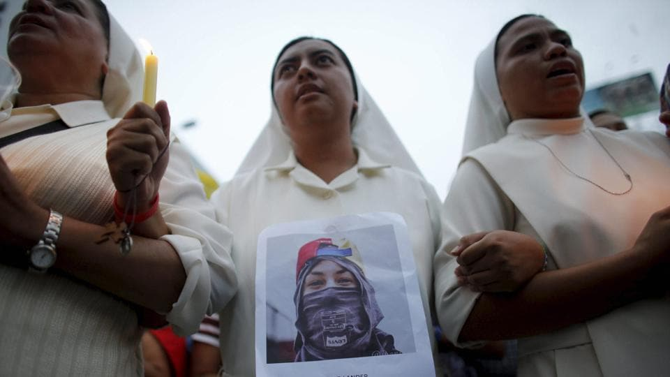 A nun wearing a photograph of protester Neomar Lander marches with others to the site where he died in Caracas, Venezuela. (AP)