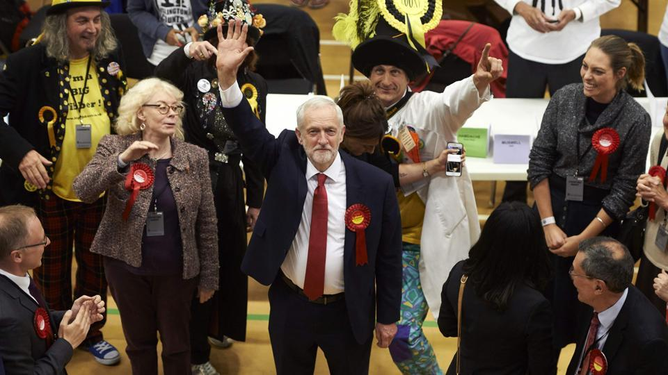 A smiling Jeremy Corbyn (C), Labour party leader, waves after arriving at the count centre in Islington, London. The main opposition Labour party, is on course to increase its number of seats from 229 to 266, according to the joint exit poll by Sky, the BBC and ITV.  (Niklas Halle'n/AFP)