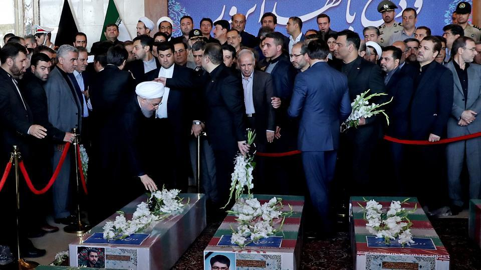 A handout picture provided by the Iranian Presidency on June 9, 2017 shows Iran's President Hassan Rouhani touching a coffin during the funeral of the victims of twin attacks in Tehran earlier in the week.