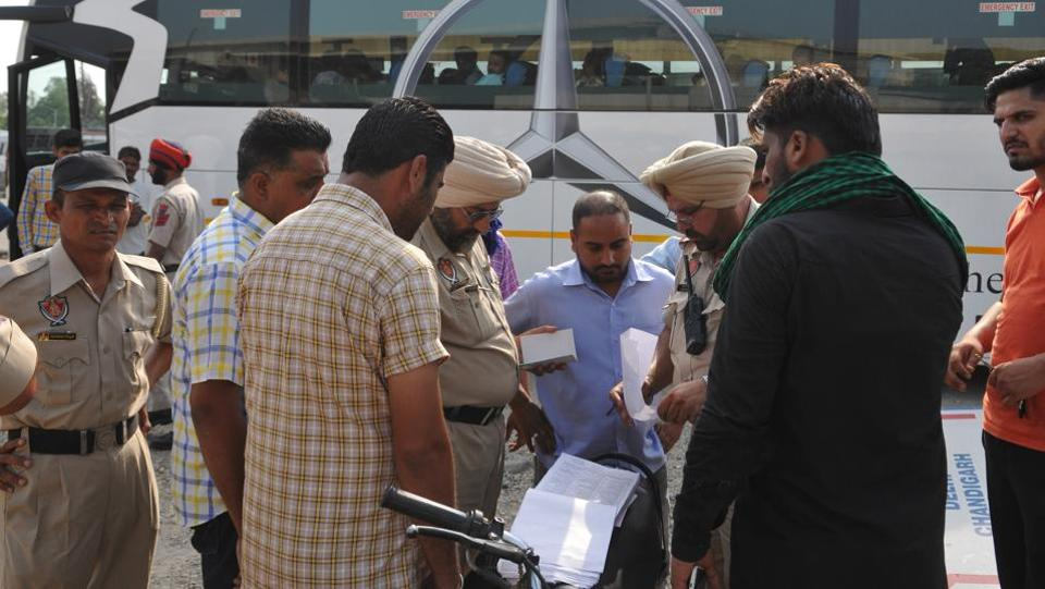 Vigilance officials along with city police checking the documents of buses at PAP Chowk in Jalandhar on Friday.