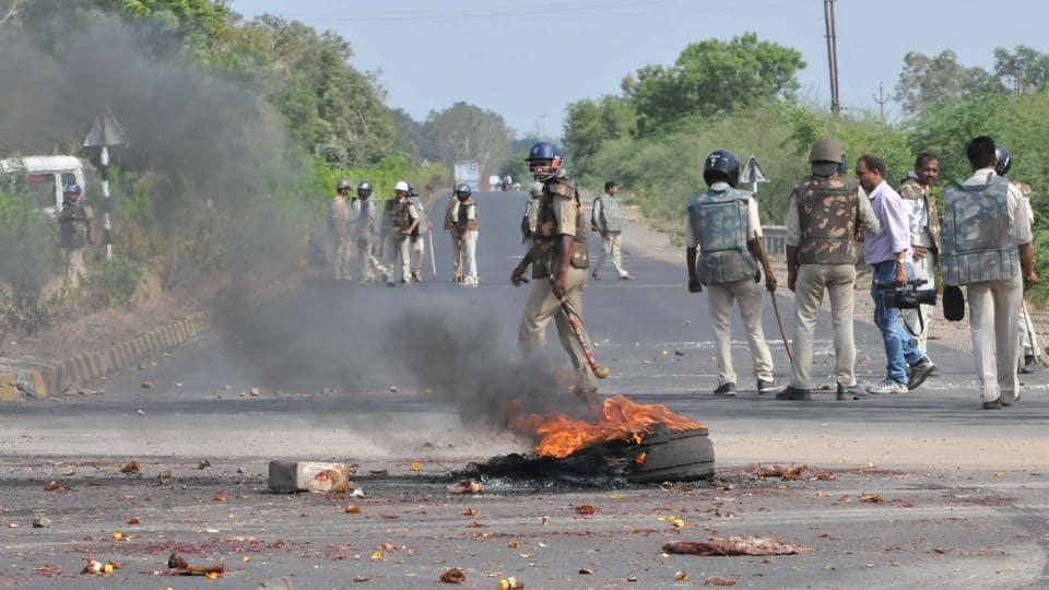 Police patrolling the Mhow- Neemuch highway amid burning tyres of a truck in Mandsaur, Madhya Pradesh.