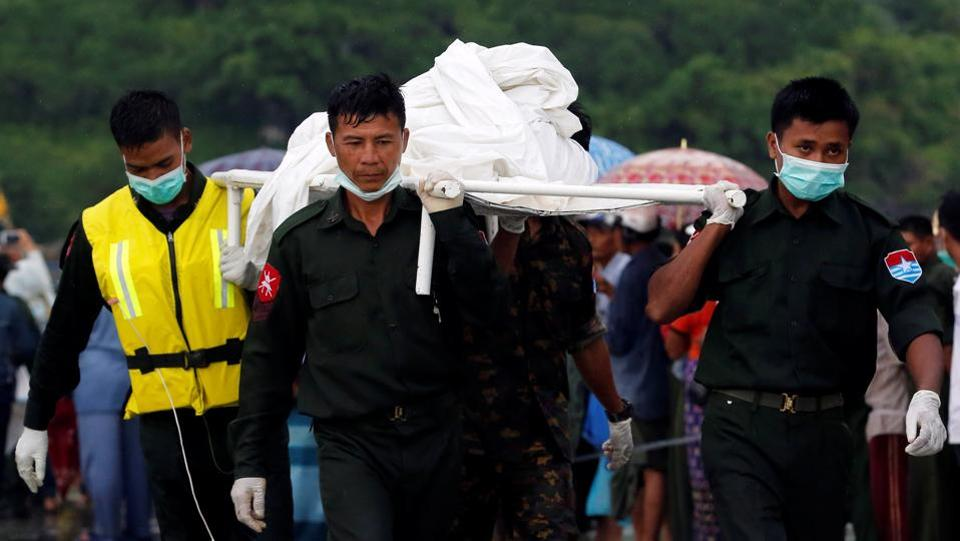 Military soldiers carry dead bodies from a crashed military plane outside Launglon township, Myanmar. (Soe Zeya Tun / REUTERS)