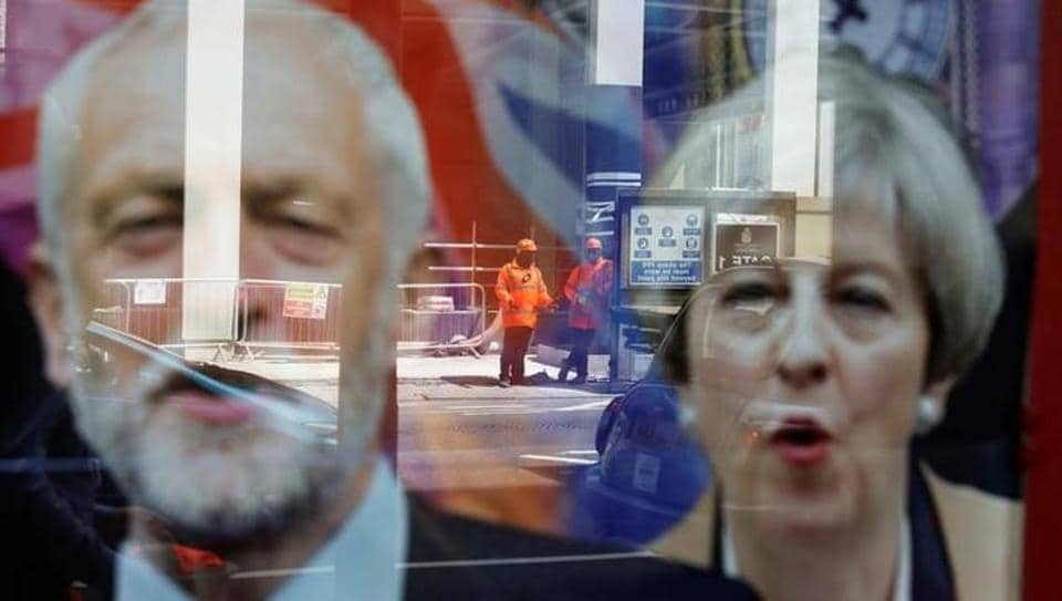 Workers in protective equipment are reflected in the window of a betting shop with a display inviting customers to place bets on the result of the general election with images of Britain's Prime Minister Theresa May and opposition Labour Party leader Jeremy Corbyn, in London.