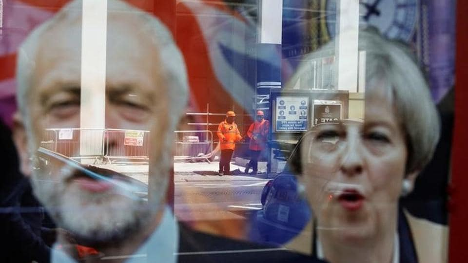 Workers in protective equipment are reflected in the window of a betting shop with a display inviting customers to place bets on the result of the British general election with images of Prime Minister Theresa May and opposition Labour Party leader Jeremy Corbyn, in London on June 7, 2017.