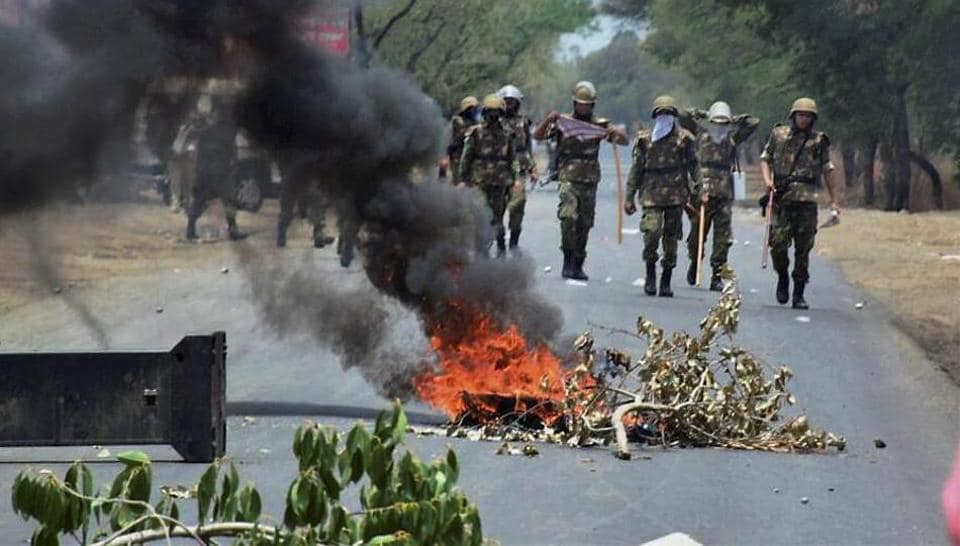 Police personnel patrol a stretch of the Indore-Bhopal highway frequented by protesters on Friday.