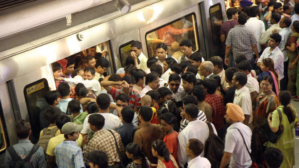 A massive crowd tries to enter a train coach at Rajiv Chowk metro station in central Delhi.