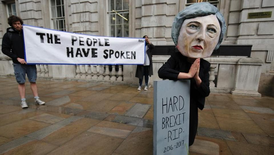 A demonstrator wears a mask depicting Britain's Prime Minister Theresa May and poses with a mock gravestone bearing the words