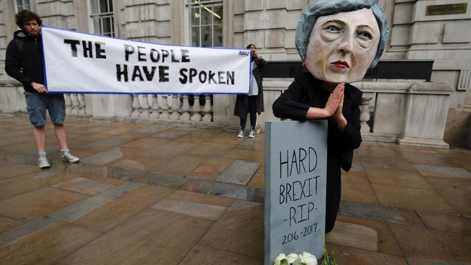 A demonstrator wears a mask depicting Britain's Prime Minister and leader of the Conservative Party Theresa May, poses with a mock gravestone bearing the words