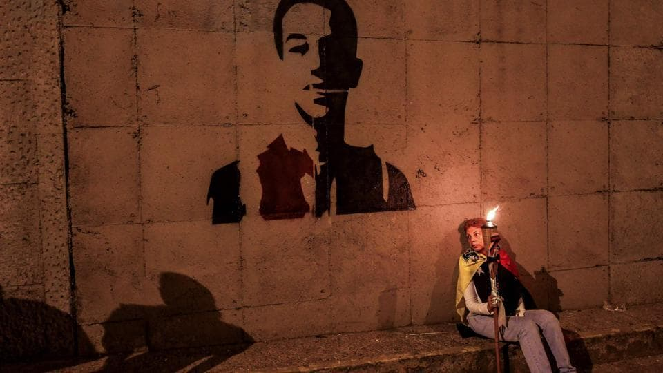 A woman holds a flaming torch next to a stencil of the face of young activist Neomar Lander, who died  during a protest against the government of President Nicolas Maduro in Caracas.  (Luis Robayo/AFP)