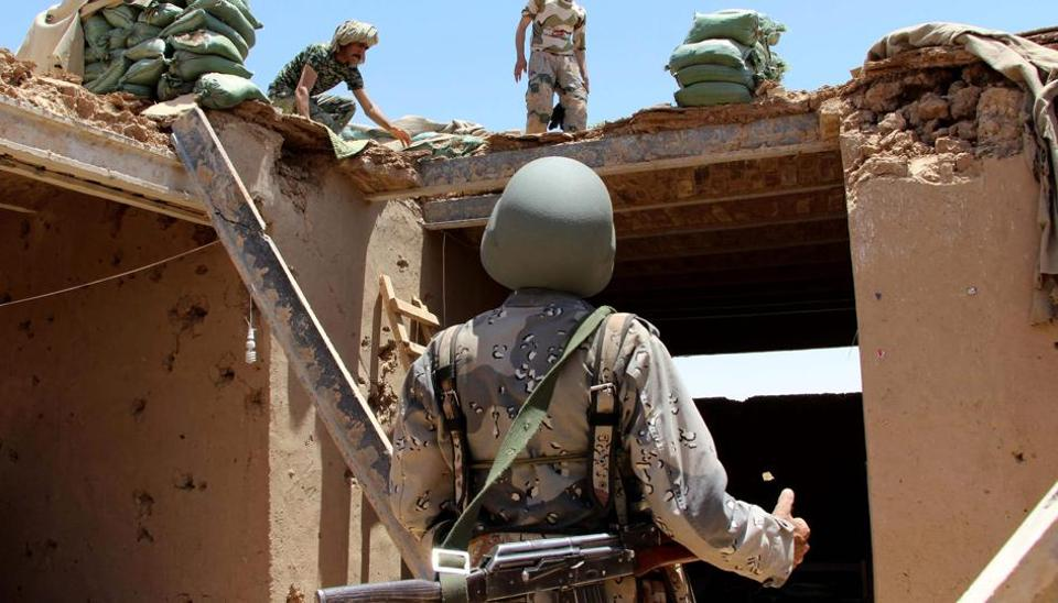 Afghan Border Police personnel walk through an outpost damaged in an airstrike in the Nad Ali district of Helmand province on June 10, 2017.