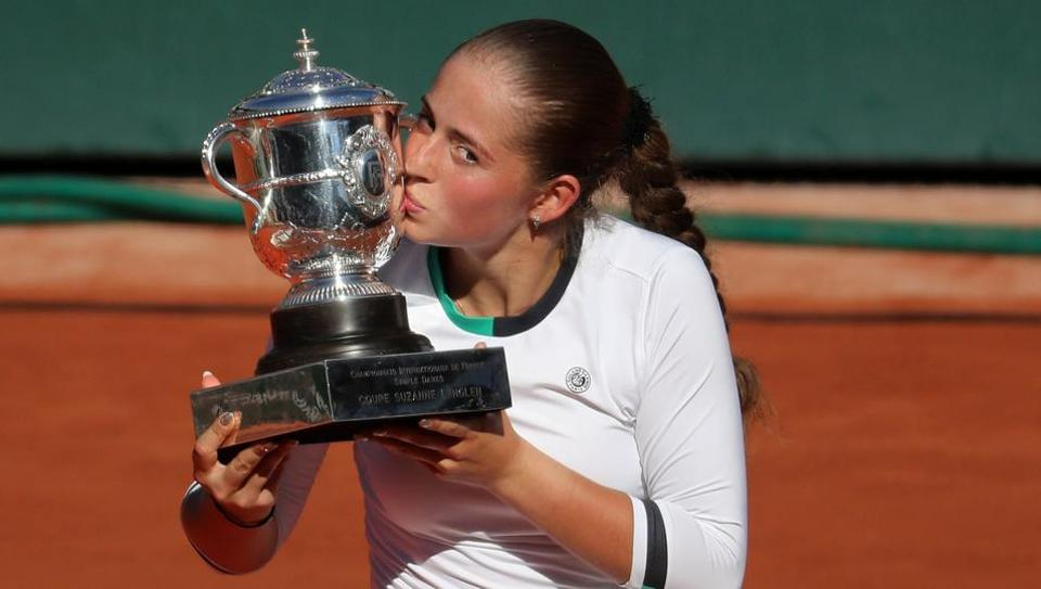French Open champion Jelena Ostapenko celebrates by kissing the trophy after winning the final against Simona Halep.