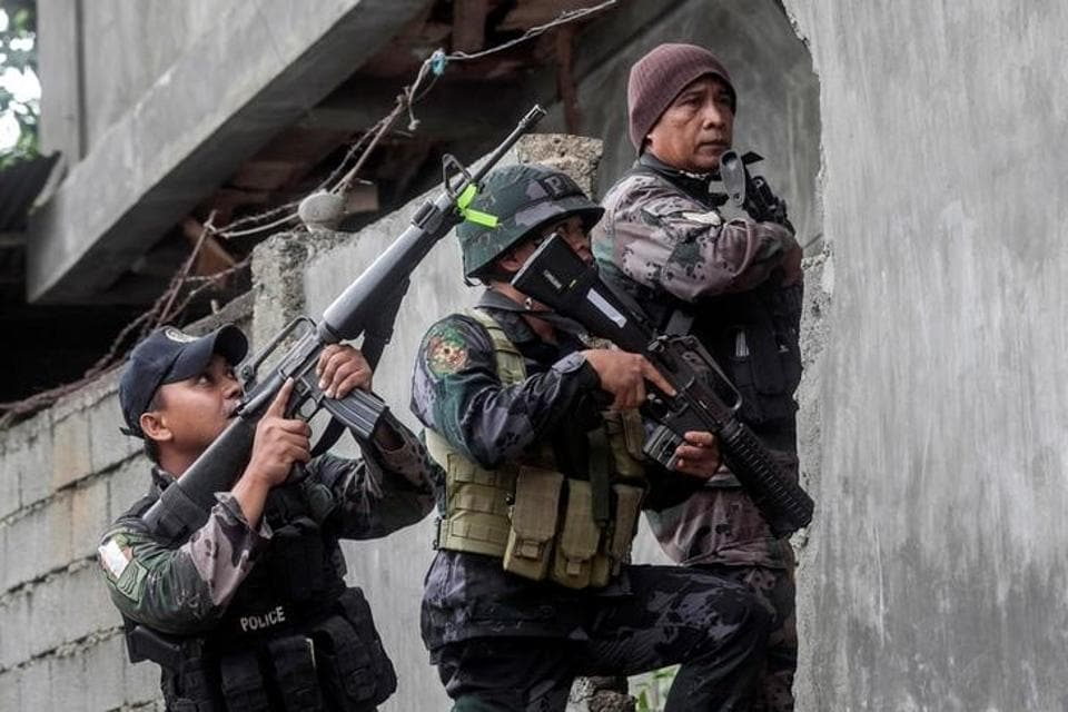 A joint group of police and military forces conduct a house-to-house search in Marawi city.