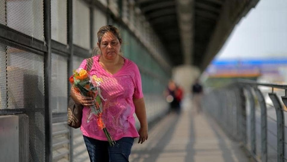A woman crosses a bridge over the Rio Grande river at a pedestrian port of entry from Mexico to the United States. (REUTERS)