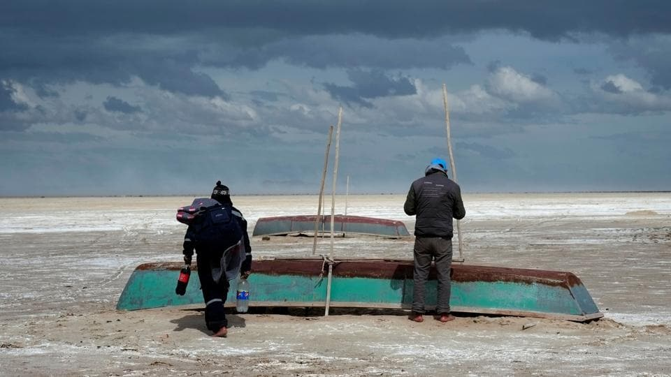 Fishermen and their boats are seen, where a slight water recovery is observed at Poopo Lake, Oruro, Bolivia. (David Mercado  / REUTERS)